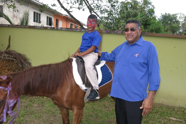 Chairman of the Sangre Grande Regional Corporation, Mr. Terry Rondon took the time to assist this young participant of the Autism Awareness Event at Monte Cristo Park, Sangre Grande.