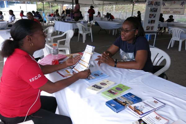 Staff of the Ministry interact with a resident of the Carenage Community during the Proactive Communities Outreach
